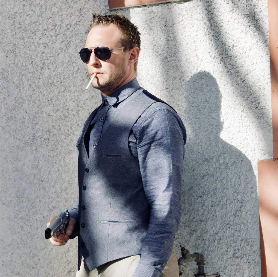 Schauspieler mit Waffe und Sonnenbrille am rauchen