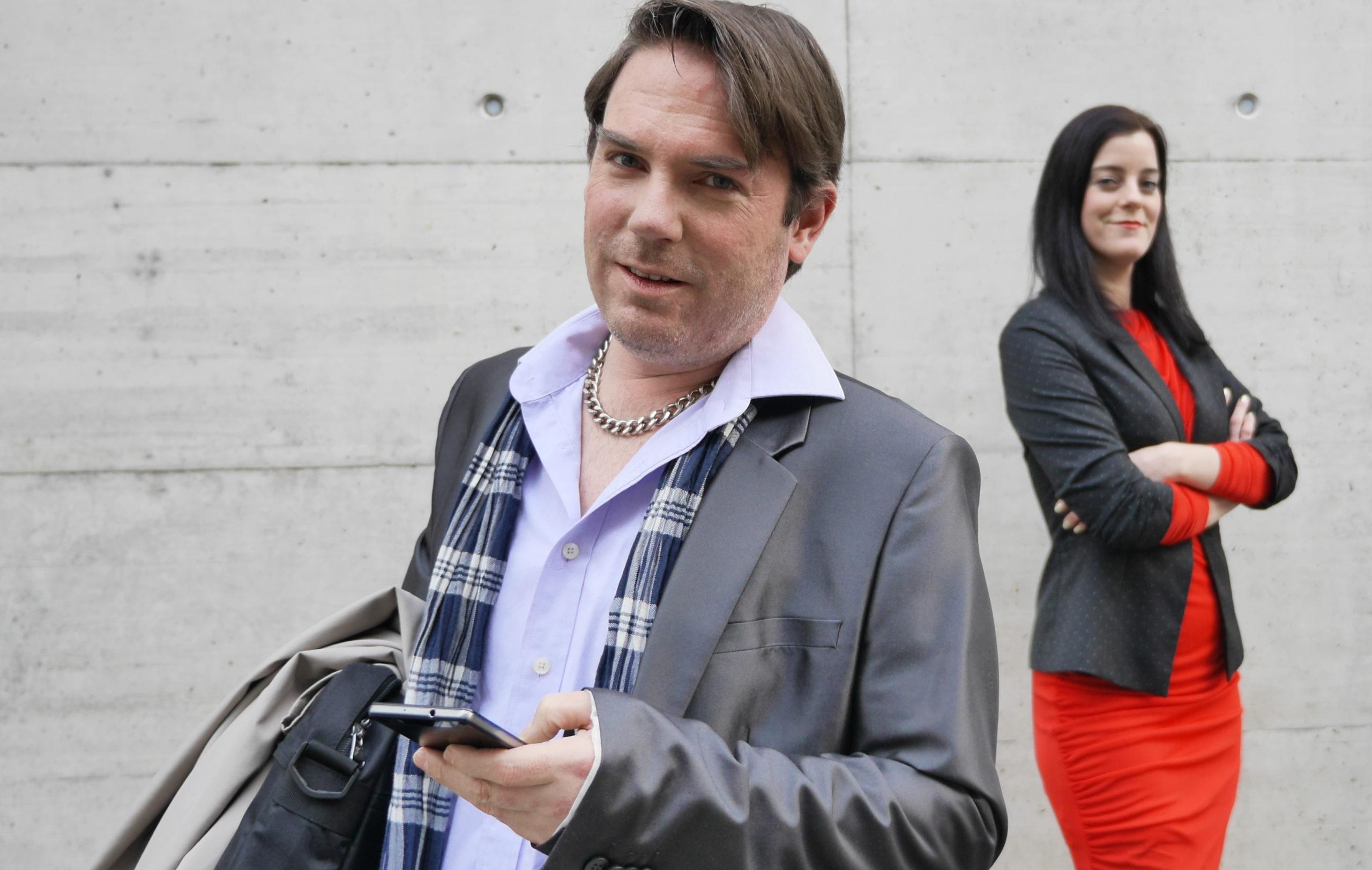Mann am Handy im Vordergrund, Frau mit verschränkten Armen im Hintergrund