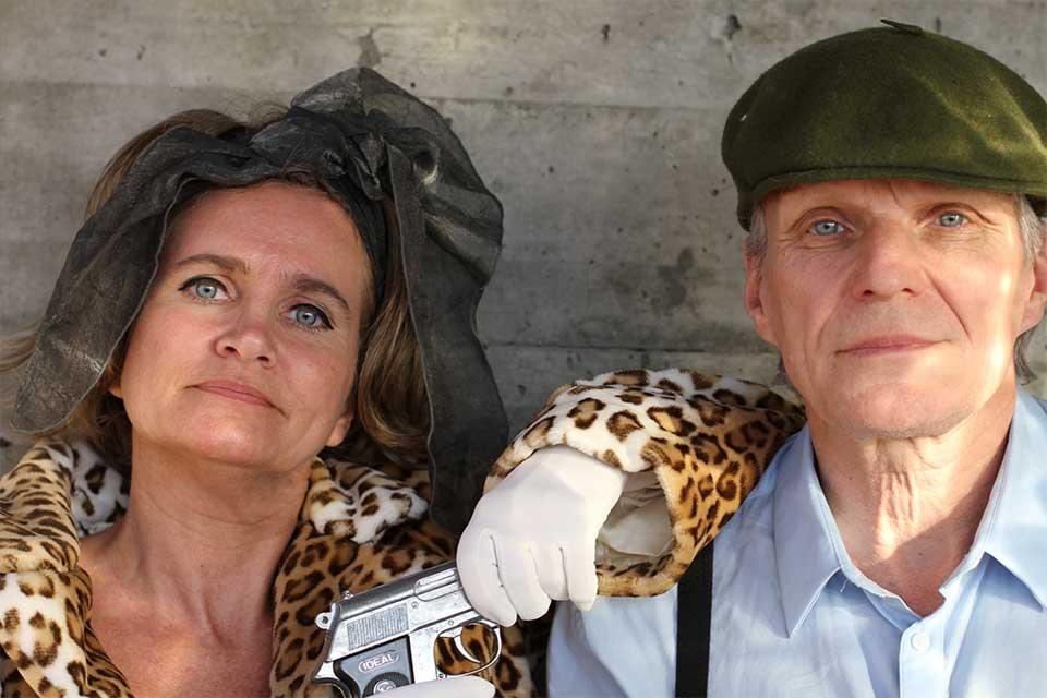 Schauspielerpaar: Frau mit Leomantel und Waffe, Mann mit grüner Kappe und Hemd