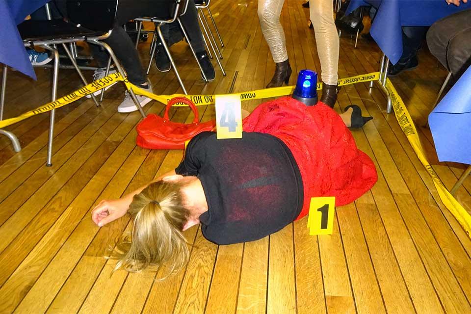 Opfer am Boden während eines Krimidinners