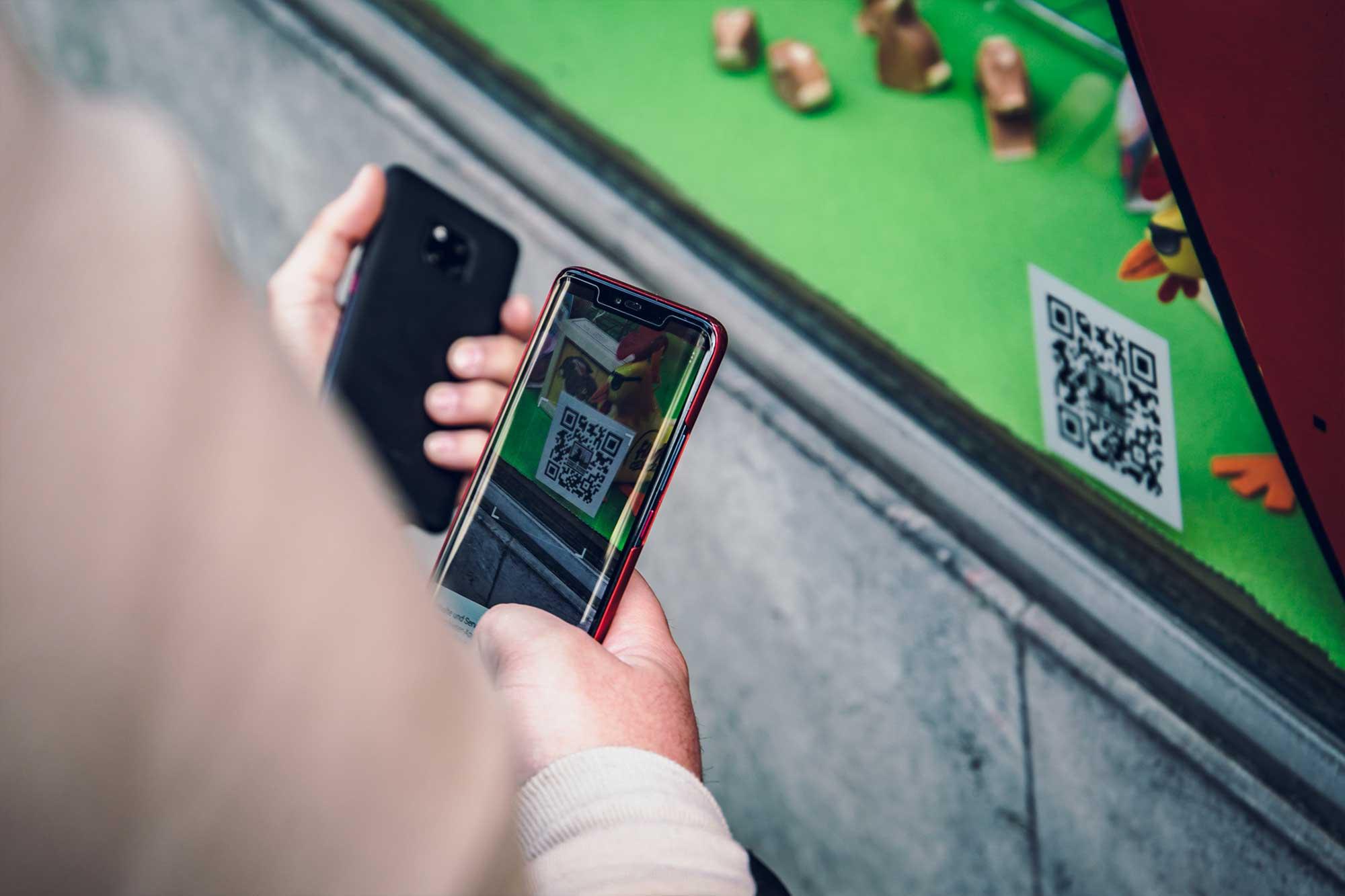 Team scannt mit Handy einen QRCode