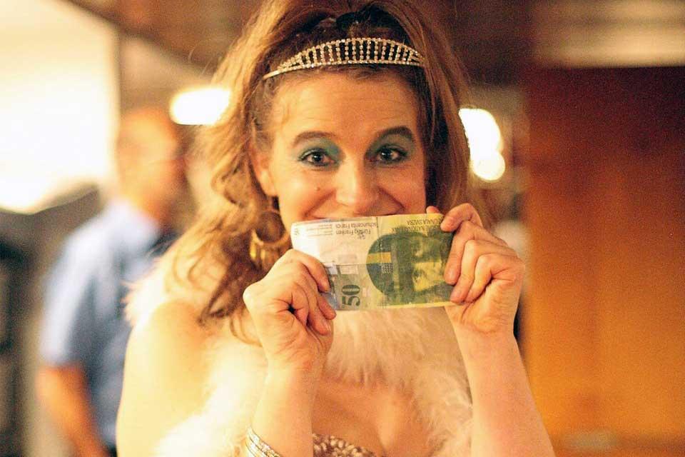 Schauspielerin als Prinzessin und mit Geldschein in der Hand während des Krimifalls: Jackpot Prinzessin