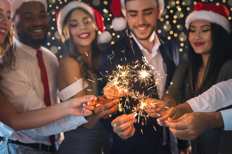 Firmenfeier zu Weihnachten - Mitarbeiter mit Wunderkerzen in der Hand