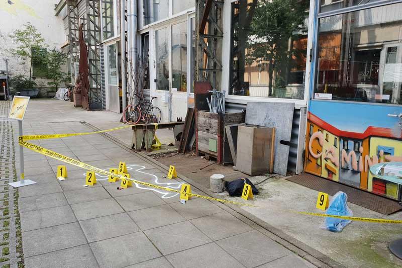 Abgesperrter Tatort einer Leiche mit verschiedenen Hinweisen für die Ermittlungen