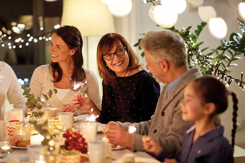 Familie mit allen Generationen sitzt zusammen am Tisch mit Wunderkerzen