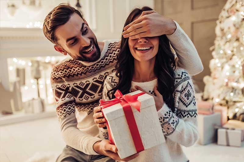 Mann gibt seiner Frau sein Weihnachtsgeschenk und hält währenddessen ihre Augen zu