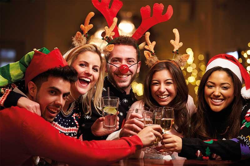 Kollegen während der Weihnachtsfeier mit Sekt und Cocktails
