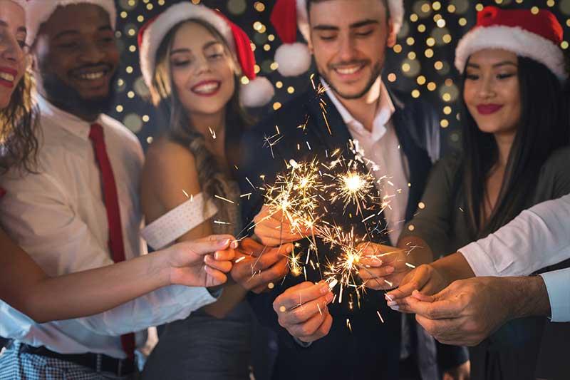 Kollegen während der Weihnachtsfeier mit Wunderkerzen