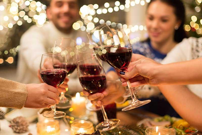 Freunde während dem Weihnachtsessen mit Wein