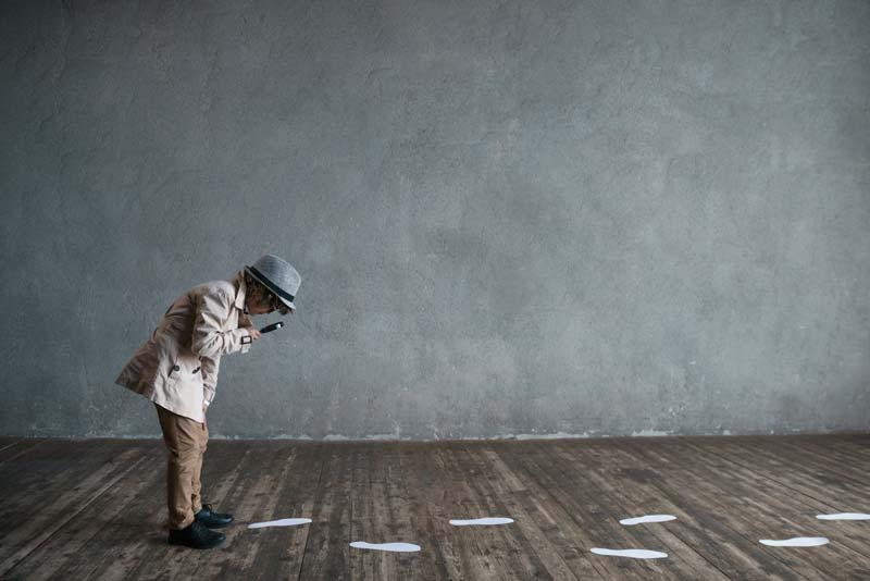 Kleiner Junge schaut durch eine Lupe und folgt den Schritten, die auf dem Boden zu sehen sind