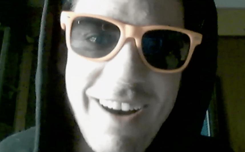 Mann mit Sonnenbrille spielt Online Krimi von Stadt-Krimi und lacht