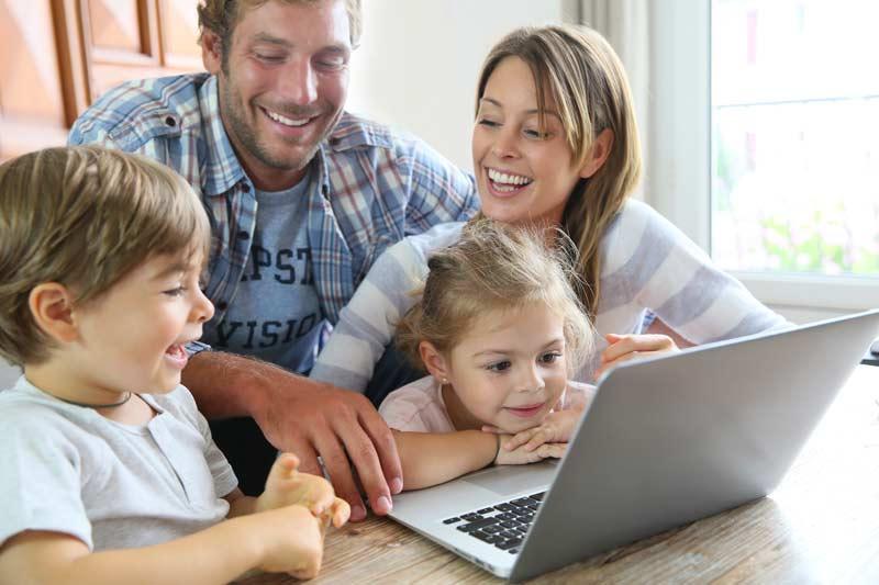 Eltern mit Kinder sitzen zu Hause vor dem Laptop