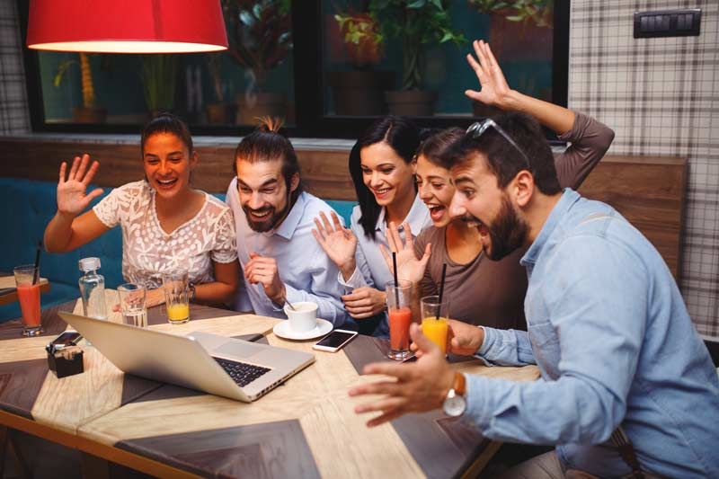 Gruppe von Freunden während einem Video Call am Laptop