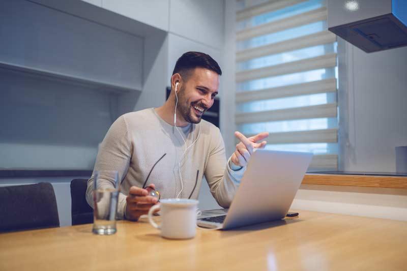 Lachender Mitarbeiter während eines Video Calls im Konferenzzimmer