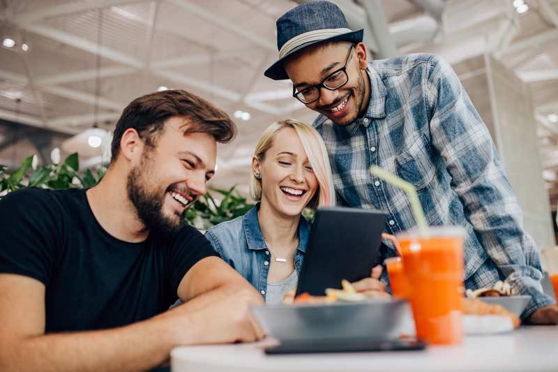 Drei Freunde während einem Video Call in einem Cafe
