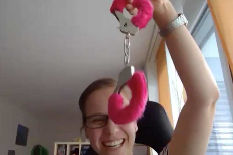 Junge, lachende Frau mit pinken Handschellen in der Hand