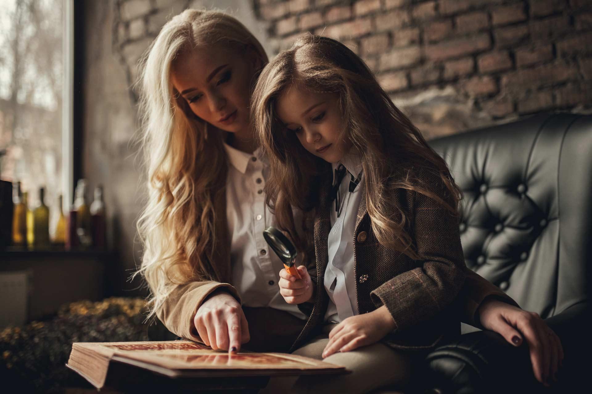 Mutter und Tochter sitzen auf dem Sofa und versuchen anhand eines alten Fotoalbums das Rätsel der Krimibox zu lösen