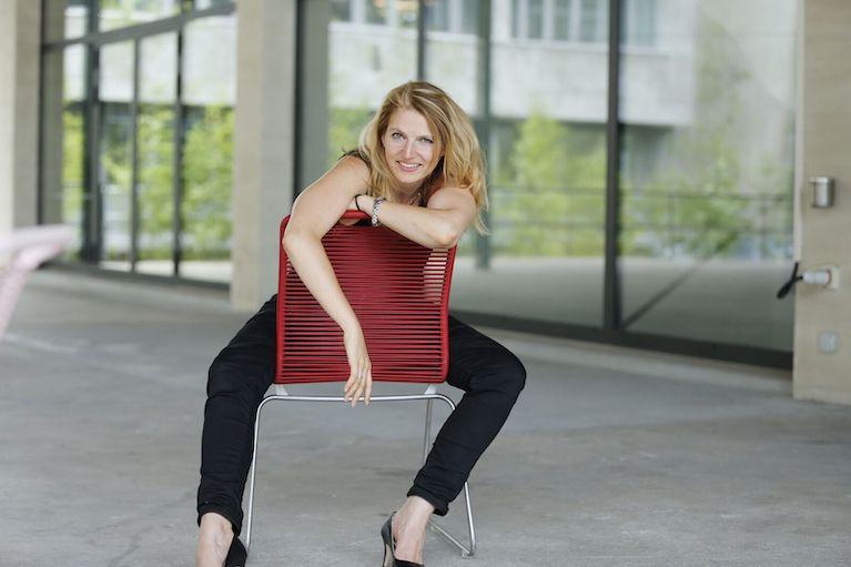 Nathalie Samelie sitzend auf einem roten Stuhl