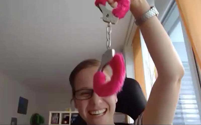 Online Krimi Teilnehmerin mit pinken Handschellen in der Hand