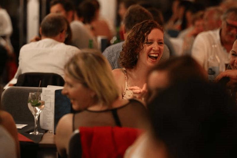 Lachende Frau sitzt am Tisch beim Krimidinner