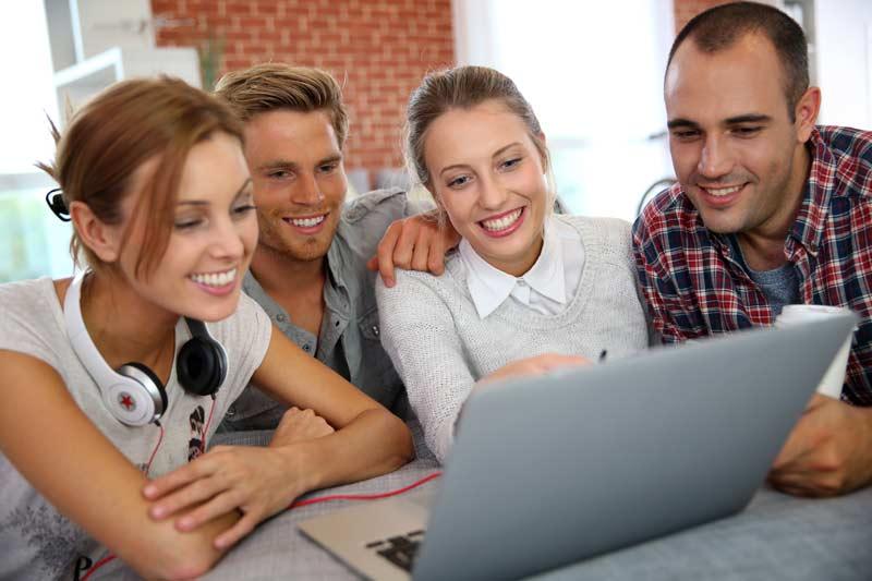Freunde sitzen zusammen vor dem Laptop