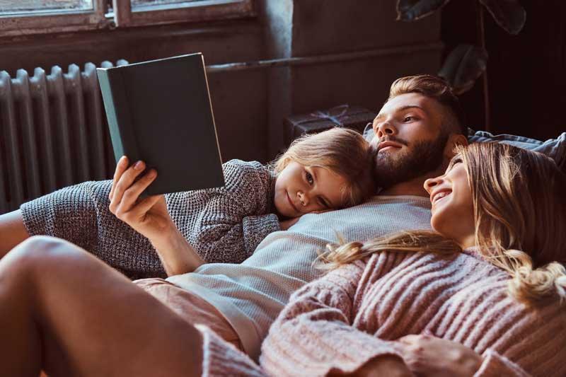Familie liest zusammen in einem Buch