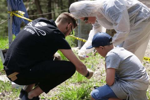 Spurensuche vor Ort bei dem die Ermittler mit einer Lupe und einem Kind die Hinweise im Gras besichtigen