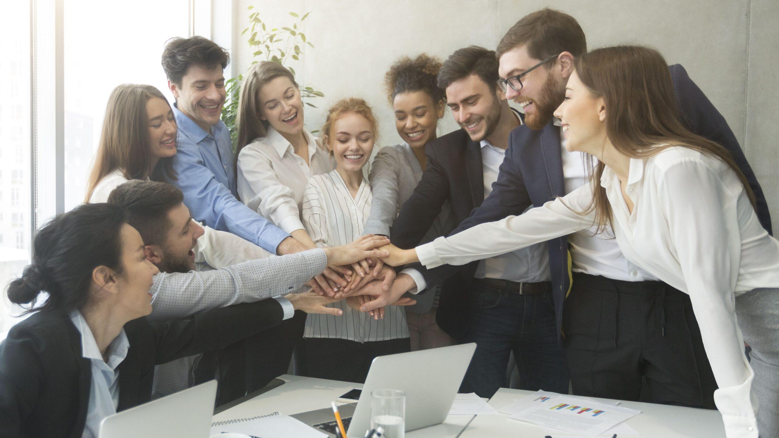 Ein Team legt im Office die Hände aufeinander und zeigt seinen Teamgeist